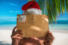 Turist- man med den Santa Claus hatten som kopplar av på tropisk öbea Royaltyfri Foto