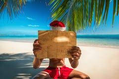 Turist- man med den Santa Claus hatten som kopplar av på tropisk öbea Arkivfoton