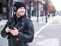 Turist- man som använder smartphonen för att lyssna till musiken via hörlurar, medan gå vid vinterstaden Royaltyfri Foto