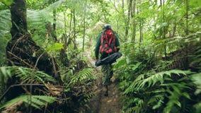 Turist- man som går på banan som fotvandrar i tropisk rainforestbaksidasikt Resa mannen med ryggsäcken som går i lös djungel lager videofilmer