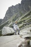 Turist med ryggsäcken som sitter på stenblocket i berg royaltyfri fotografi