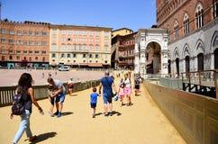 turist nära Palazzo Publico i det Piazza del Campo stadshuset av Siena, Tuscany, Italien arkivbild