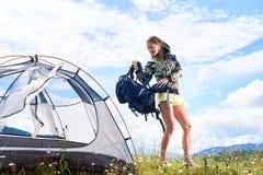 Turist- near fotvandra för kvinna i bergslingan som tycker om solig morgon för sommar i berg, tältet arkivfoton