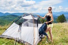 Turist- near fotvandra för kvinna i bergslingan som tycker om solig morgon för sommar i berg, tältet royaltyfri fotografi