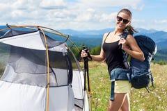 Turist- near fotvandra f?r kvinna i bergslingan som tycker om solig morgon f?r sommar i berg, t?ltet arkivbilder