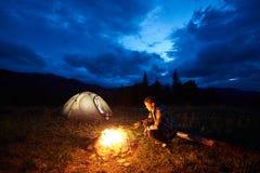 Turist- near vila för kvinna på natten som campar i berg, lägereld och tältet under molnig himmel för aftonen royaltyfria foton