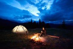 Turist- near vila för kvinna på natten som campar i berg, lägereld och tältet under molnig himmel för aftonen arkivfoto