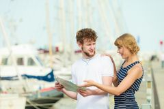 Turist- par i marina som upp ser riktningar på översikt Arkivfoton