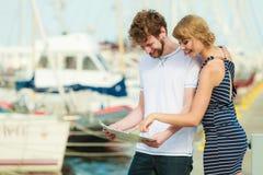 Turist- par i marina som upp ser riktningar på översikt Arkivbilder