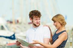 Turist- par i marina som upp ser riktningar på översikt Arkivfoto