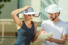 Turist- par i staden som upp ser riktningar på översikt Royaltyfri Foto
