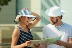 Turist- par i staden som upp ser riktningar på översikt Royaltyfria Bilder