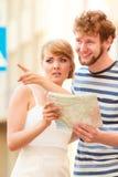 Turist- par i staden som upp ser riktningar på översikt Arkivfoton