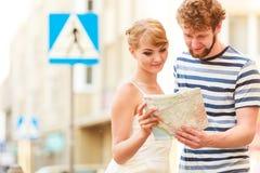 Turist- par i staden som upp ser riktningar på översikt Arkivfoto