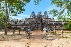 Turist- par som cyklar runt om den Angkor templet, Cambodja Byggnad för Ta Keo fördärvar i djungeln Resa för Eco vänligt turism arkivfoton