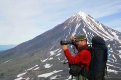 Turist-photographer. Kamchatka.Turist-photographer on the background of Koryaksky volcano Royalty Free Stock Image