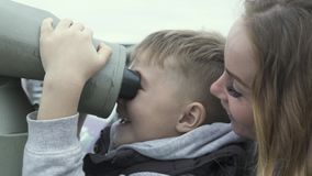 Turist- pojke som ser stadspanorama vid turist- kikare medan moder för lopp tillsammans Turist- pojke som ser kikare stock video
