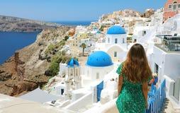 Turist- resa i Santorini, Oia ö i flicka för semester för Grekland, Europa loppsommar som kopplar av på sikten av tre blåa kupole fotografering för bildbyråer