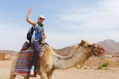 Turist- ridning för ung caucasian kvinna på kamel Fotografering för Bildbyråer