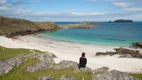 Turist- sammanträde för ung kvinna framme av en vit strand för öken Royaltyfria Bilder