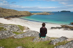 Turist- sammanträde för ung kvinna framme av en vit strand för öken Arkivfoton