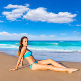 Turist- sammanträde för brunett, i att garva för strandsand som är lyckligt Royaltyfri Foto