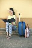 Turist- sammanträde för ung kvinna med bagage och en loppbroschyr I Arkivbilder