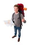 Turist- seende översikt för ung attraktiv fotvandrare som bär den stora ryggsäcken som ger upp tummen Royaltyfri Bild