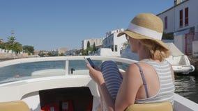 Turist- segling för kvinna på ett litet fartyg på kanalen Använd mobiltelefoner Empuriabrava Spanien lager videofilmer