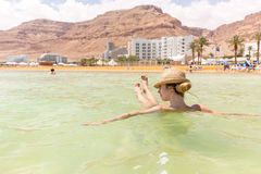 Turist- simning för ung kvinna som svävar salt vatten, dött hav Arkivbilder