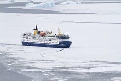 Turist- skepp som bryter is i kanalen av den antarktiska Peninsuen Arkivbilder