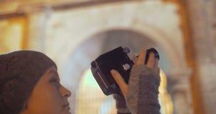 Turist som använder den retro kameran för att skjuta nattcoliseumen stock video