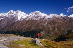 Turist som fotvandrar i schweiziska fjällängar Fotografering för Bildbyråer