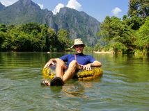 Turist som går ner Nam Song River i ett rör som omges av karst arkivbilder
