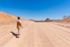 Turist som går på korsning för väg 4x4 den färgrika öknen på Twyfelfontein, i den majestätiska Damaralanden Brandberg, scenisk lo Arkivfoto