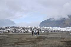 Turist som går till den is- lagun i Island Royaltyfri Fotografi