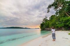 Turist som håller ögonen på ett avslappnande solnedgångsammanträde på stranden i de avlägsna Togean öarna, centrala Sulawesi, Ind Royaltyfri Bild