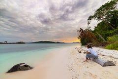 Turist som håller ögonen på ett avslappnande solnedgångsammanträde på stranden i de avlägsna Togean öarna, centrala Sulawesi, Ind Arkivfoto