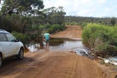 Turist som kontrollerar djupet av en floodway i den australiska vildmarken royaltyfria foton
