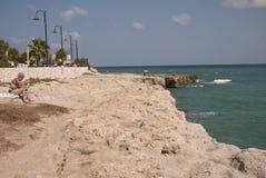 Turist som solbadar i Torre Sant Andrea Arkivfoto