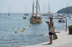 Turist som tar bilder av segelbåtar nära kusten Arkivfoton