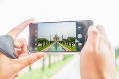 Turist som tar foto av Haj Mahal med mobiltelefonen Arkivfoton
