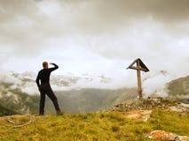 Turist- ställning på stenig siktspunkt och hålla ögonen på in i den dimmiga alpina dalen Wooden cross at a mountain peak Kors öve Arkivbild