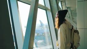 Turist- ställningar på fönstret i flygplatsterminal stock video