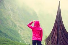 Turist- stående near gammalt träviking fartyg i norsk natur Arkivbilder