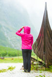 Turist- stående near gammalt träviking fartyg i norsk natur Royaltyfri Bild
