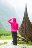 Turist- stående near gammalt träviking fartyg i norsk natur Arkivbild
