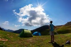 Turist- tält i läger bland äng i berget Sommarseaso royaltyfri fotografi