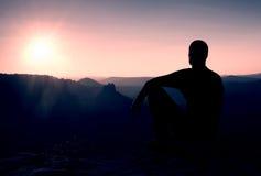 Turist- ta en vila stiligt sammanträde för den unga mannen på vagga och tycka omsikten in i dimmiga steniga berg royaltyfri fotografi