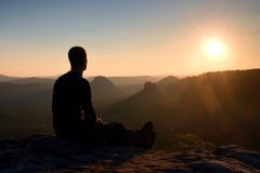 Turist- ta en vila stiligt sammanträde för den unga mannen på vagga och tycka omsikten in i dimmiga steniga berg royaltyfria bilder